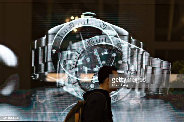 A visitor walks past a digital screen displaying luxury wristwatches during the 2017 Baselworld luxury watch and jewellery fair in Basel Switzerland...