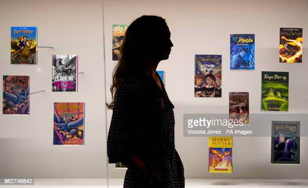 A visitor walks past a display of foreign language editions of the Harry Potter books during a press preview for the Harry Potter A History of Magic...