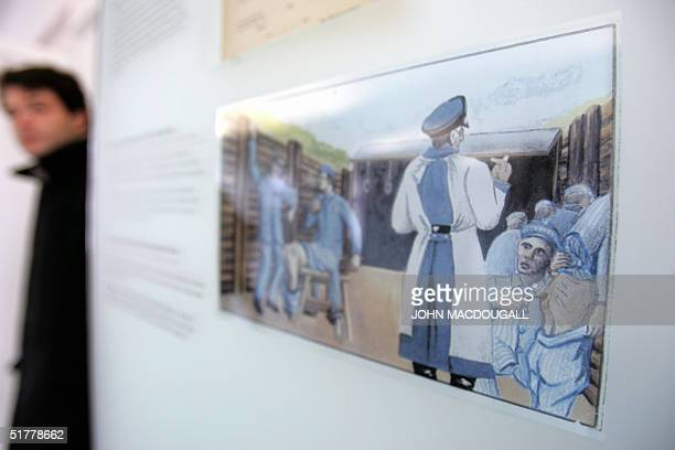A visitor walks past a drawing by a former concentration camp inmate showing a Nazi doctor overseeing corporal punishment given out to prisoners at...