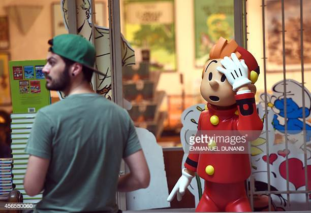 A visitor walks past a figurine of cartoon character 'Spirou' in the 'Centre Belge de la Bande Dessinee' on October 3 2014 in Brussels as it marks...