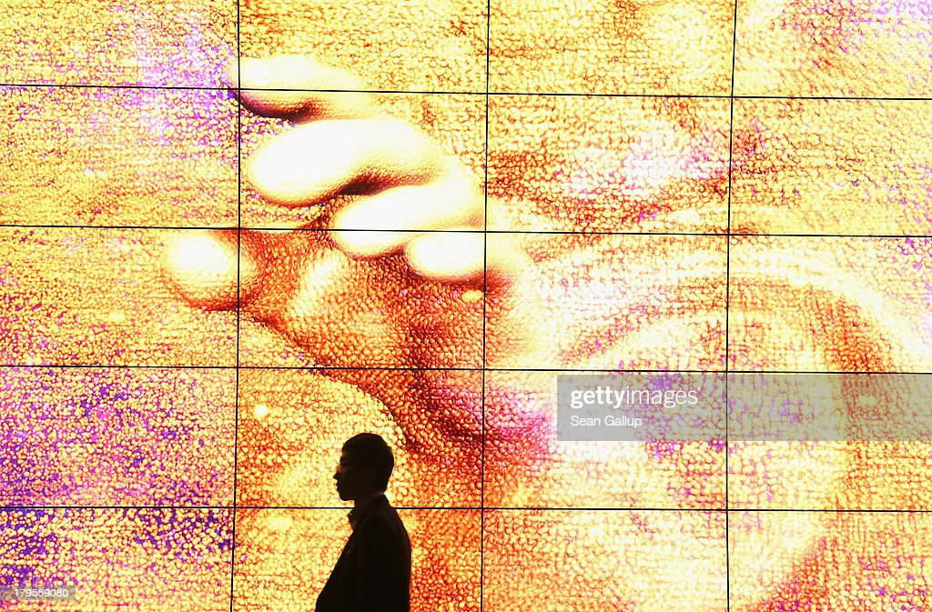 A visitor walks past a giant 3D HD presentation at the LG stand at the IFA 2013 consumer electronics trade fair on September 5, 2013 in Berlin, Germany. The 2013 IFA will be open to the public from September 6-11.