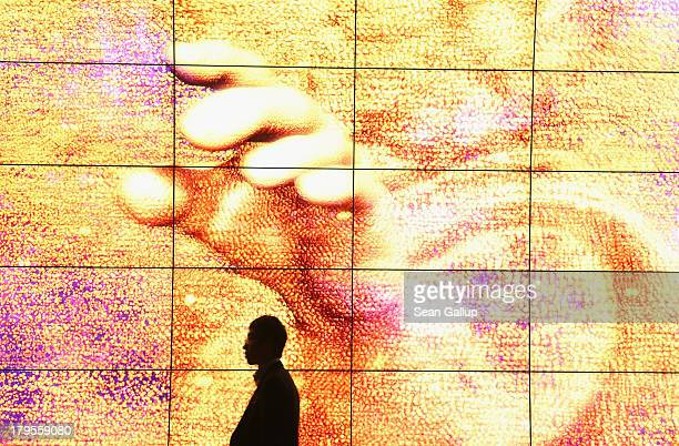 A visitor walks past a giant 3D HD presentation at the LG stand at the IFA 2013 consumer electronics trade fair on September 5 2013 in Berlin Germany...