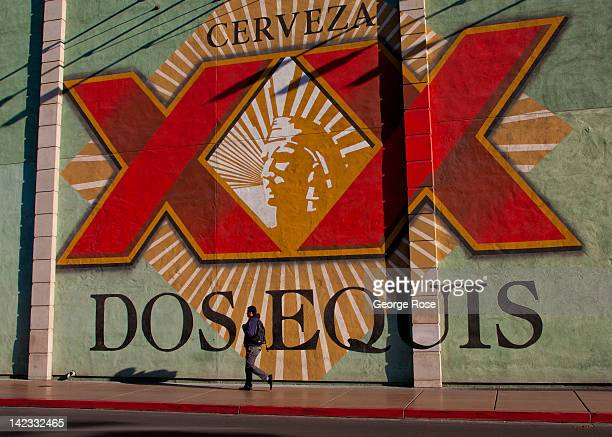 A visitor walks past a giant Dos Equis billboard located near the Monte Carlo Hotel Casino on March 18 in Las Vegas Nevada Hit hard by a fouryear...