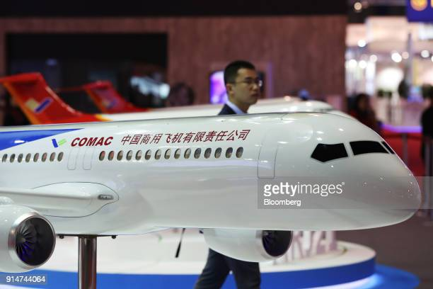 A visitor walks past a scale model of a Commercial Aircraft Corp of China Ltd aircraft at the Singapore Airshow held at the Changi Exhibition Centre...