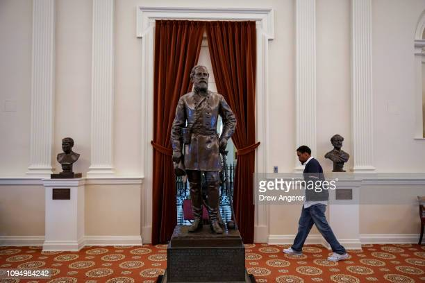 A visitor walks past a statue of Confederate General Robert E Lee stands in the Old House Chamber at the Virginia State Capitol February 7 2019 in...