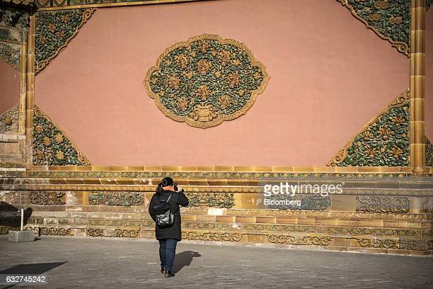 A visitor walks past a wall inside the Palace Museum at the Forbidden City in Beijing China on Thursday Nov 24 2016 Beijings Palace Museum receives...