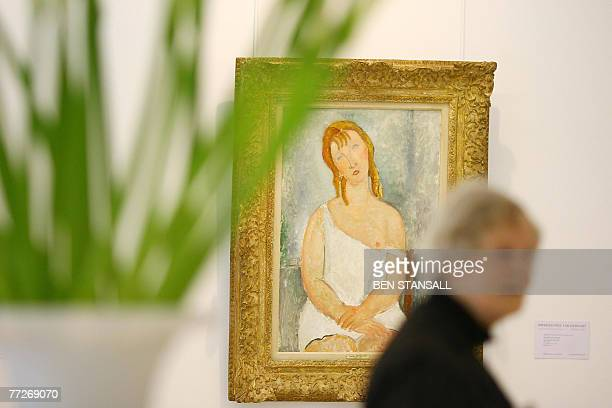 A visitor walks past Amedeo Modigliani's painting 'Jeune fille assise en chemise' at Christie's in central London 11 October 2007 Christie's launched...
