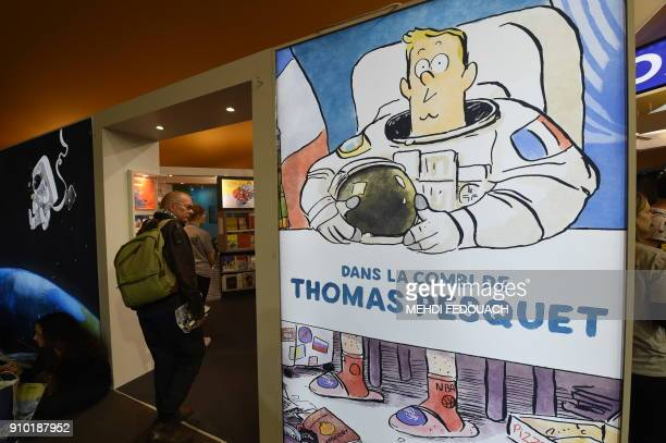 A visitor walks past an advert for Dans la combi de Thomas Pesquet comic during the 45th edition of the Angouleme International Comics Festival in...
