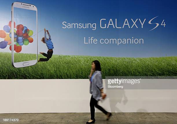 Visitor walks past an advertisement for the Samsung Electronics Co. Galaxy S4 smartphone at the World IT Show 2013 in Seoul, South Korea, on Tuesday,...