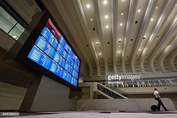 A visitor walks past an electronic board displaying market indices at the Tokyo Stock Exchange operated by Japan Exchange Group Inc in Tokyo Japan on...