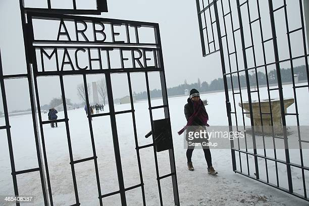 "Visitor walks past an inscription that reads: ""Arbeit Macht Frei,"" which means ""Work Leads To Freedom,"" at a gate at the Sachsenhausen concentration..."