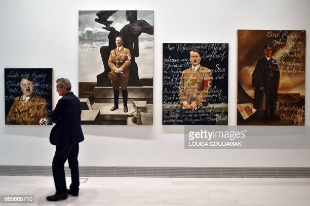 A visitor walks past artworks by PolishUS artist Piotr Uklanski and US artists McDermott McGough at the National museum of Contemporary Art in Athens...