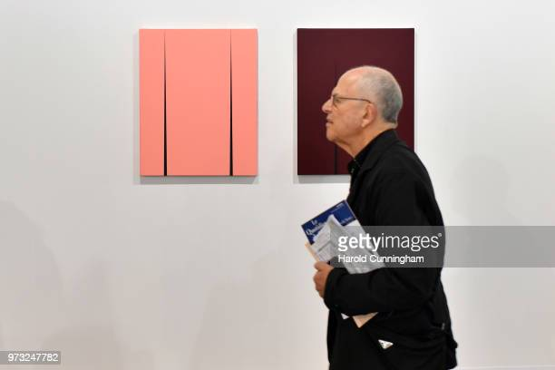 A visitor walks past artworks of Ann Edholm 'Gryning/Down' and 'Skymning/Dusk' during the press preview for Art Basel at Basel Messe on June 13 2018...