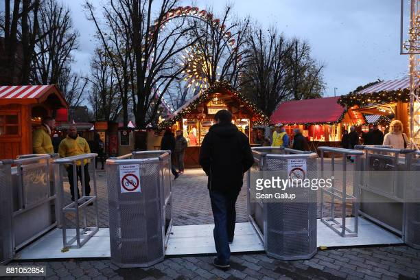 A visitor walks past concrete security barriers meant to stop vehicledriven terror attacks at the annual Christmas market at Alexanderplatz on...