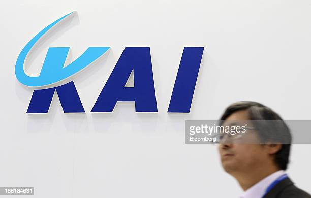 Visitor walks past Korea Aerospace Industries Ltd. Signage at the company's booth in the Seoul International Aerospace & Defense Exhibition 2013 in...