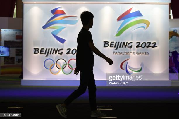 Visitor walks past logos of the upcoming Beijing 2022 Winter Olympic and Paralympic Games during the Beijing Olympic Expo marking the 10th...