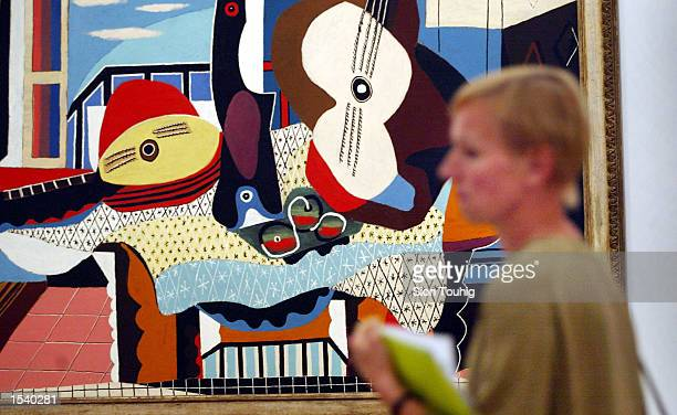 A visitor walks past 'Mandolin and Guitar' by Pablo Picasso May 7 2002 at the launch of the 'Matisse Picasso' exhibition at the Tate Modern Gallery...