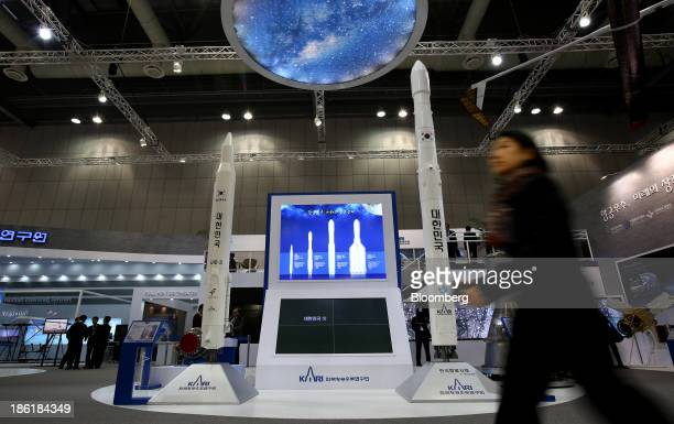 Visitor walks past models of Korea Space Launch Vehicle-1 , left, and Korea Space Launch Vehicle-2 , developed by the Korea Aerospace Research...