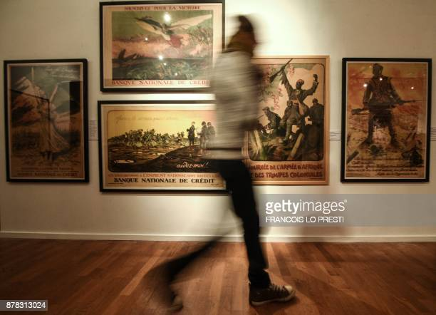 A visitor walks past old posters displayed in an exhibition on the centenary of the battle of Cambrai on November 24 2017 in Cambrai museum / AFP...