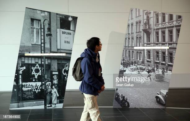 A visitor walks past photographs showing the aftermath of the 1938 Kristallnacht pogroms in the German cities of Berlin and Kassel at an exhibit at...