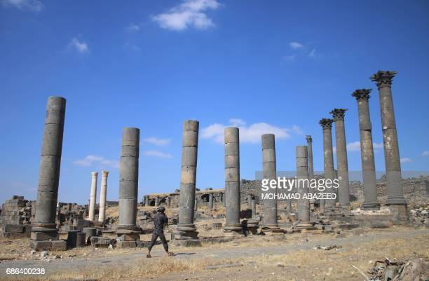 A visitor walks past Roman columns in the ancient city of Bosra alSham which is listed as a UNESCO World heritage site in the southern Syrian...