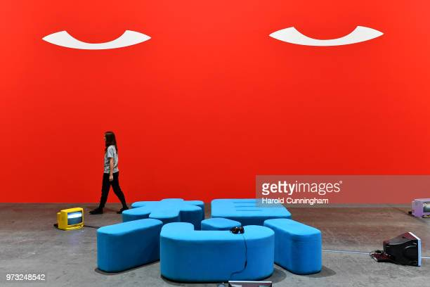 A visitor walks past the artwork of Nedko Solakov 'I miss Socialism maybe' during the press preview for Art Basel at Basel Messe on June 13 2018 in...