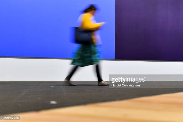 A visitor walks past the artwork of Olivier Mosset 'Untitled' during the press preview for Art Basel at Basel Messe on June 13 2018 in Basel...