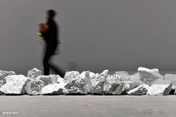 A visitor walks past the artwork of Richard Long 'Ivory Granite Line' during the press preview for Art Basel at Basel Messe on June 13 2018 in Basel...