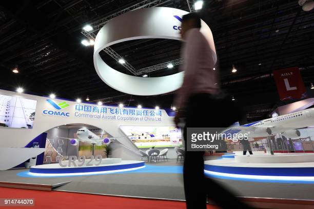 A visitor walks past the Commercial Aircraft Corp of China Ltd booth at the Singapore Airshow held at the Changi Exhibition Centre in Singapore on...