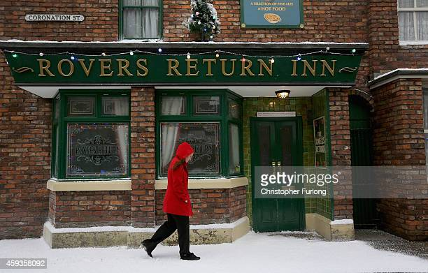A visitor walks past the famous Rovers Return as the set of television soap Coronation St are covered in fake snow for the festive season for...