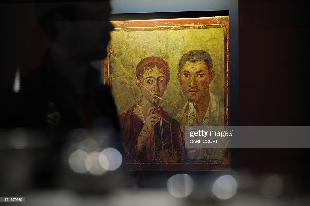 A visitor walks past the first century AD fresco protrait of baker Terentius Neo and his wife, a relic of Pompeii, the Roman town that was partially destroyed in the eruption of Mount Vesuvius in AD 79, during the press preview for the 'Life and Death Pompeii and Herculaneum' exhibition at the British Museum in central London on March 26, 2013.
