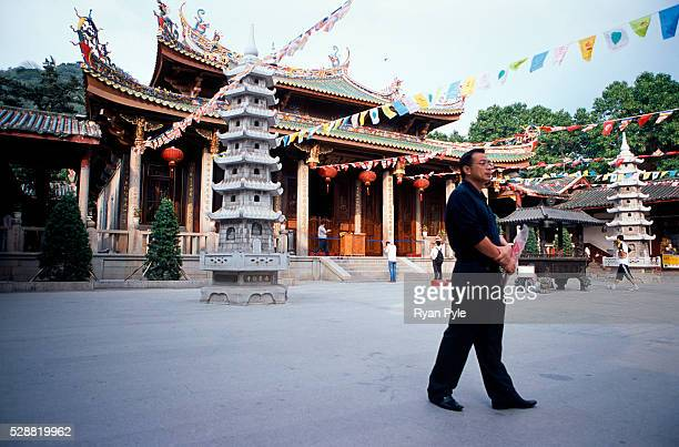 Visitor walks past the Heroic Treasure Hall at the Nanputuo Temple in Xiamen. The Nanputuo Temple is located on the southeast of Xiamen Island. It is...