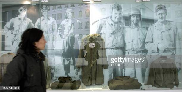 "Visitor walks past the images and old uniforms of US Air Force's ""Flying Tigers"" from World War Two who were led by late General Claire L. Chennault..."