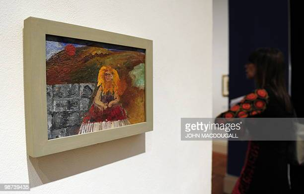 A visitor walks past the painting 'SelfPortrait Inside a Sunflower' the last selfportrait by Mexican artist Frida Kahlo during a press preview on...