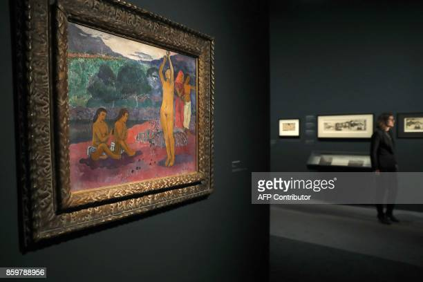 A visitor walks past the painting 'The Invocation' by French painter Paul Gauguin during the exhibition entitled 'Gauguin the alchimist' at the Grand...