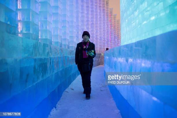 A visitor walks through ice sculptures during the annual Harbin Ice and Snow Festival in Harbin in China's northeast Heilongjiang province on January...