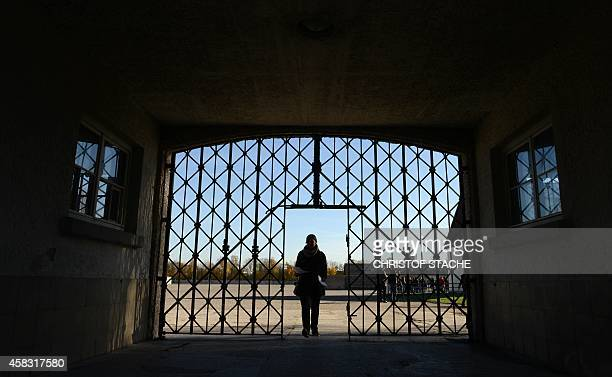 A visitor walks through the entrance gate without the door of the former concentration camp in Dachau southern Germany pictured on November 3 2014...