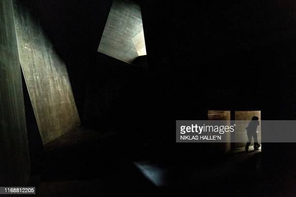 A visitor walks through the interior of an art installation entitled 'Cave' during a presspreview at The Royal Academy of Arts in London on September...