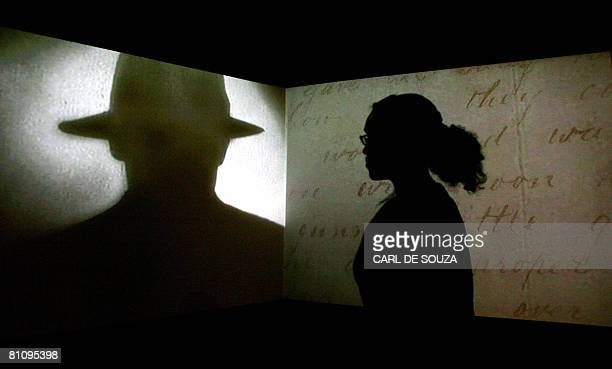 A visitor watches a black and white projection during a press preview of the 'Jack the Ripper and the East End' exhibition at Museum in Docklands in...