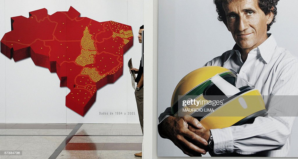 A visitor watches a video of late thrice Formula One world champion Brazilian Ayrton Senna, next to a picture of former French driver Alain Prost holding a Senna's replica helmet, during a promotional event to collect funds for the Ayrton Senna's Institute 13 April, 2006 in Sao Paulo, Brazil. AFP PHOTO/Mauricio LIMA