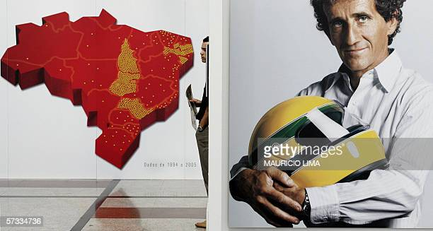 A visitor watches a video of late thrice Formula One world champion Brazilian Ayrton Senna next to a picture of former French driver Alain Prost...
