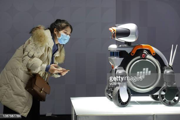 Visitor watches an intelligent inspection robot during the 2020 World Industrial Design Conference at Yantai International Expo Center on November...