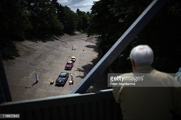A visitor watches as cars compete in a driving test on the banked race track at The Brooklands Double Twelve Motorsport Festival on June 18 2011 in...
