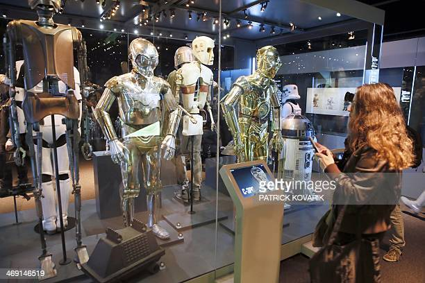 A visitor watches costumes of robots including famed C3PO from the Star Wars film series which are displayed during the presentation of the...