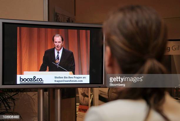 A visitor watches James Gorman chief executive officer of Morgan Stanley speak on a television screen at the the Banks in Crisis conference in...