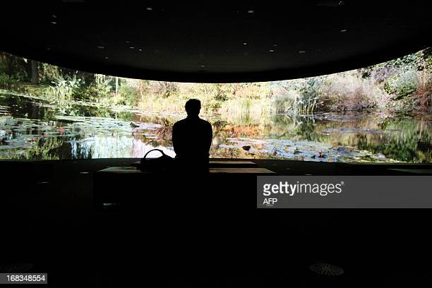 A visitor watches screening footage from Monet's garden at Giverny during the preview of the Melbourne Winter Masterpiece exhibition 'Monet's Garden...