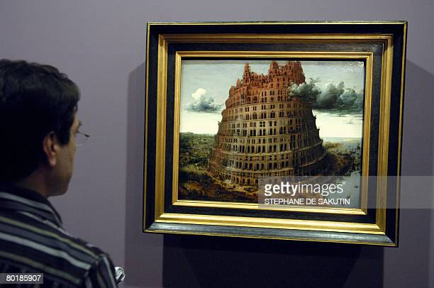 A visitor watches the painting called 'The little tower of Babel' by Flemish artist Peter Brueghel the Elder is presented during the exhibition...