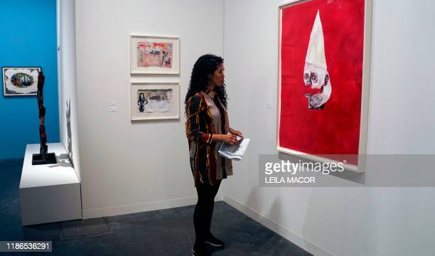A visitor watches the work of US artist Wardell Milan Amerika Klansman David representing a deconstructed face with a KKK hood during a preview on...