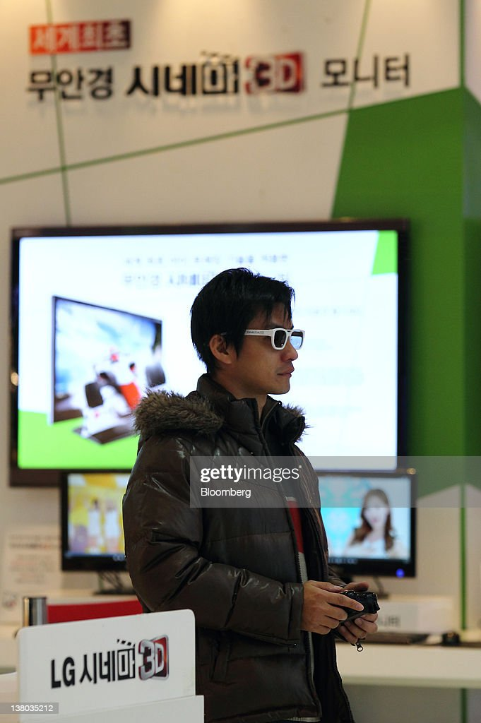A visitor wearing 3-D glasses looks at a LG Electronics Inc. 3-D smart television at the company's showroom in the COEX mall in Seoul, South Korea, on Wednesday, Feb. 1, 2012. LG Electronics Inc., South Korea's second-largest electronics maker, posted the first profit at its handset business in seven quarters, helping shares reverse earlier losses in Seoul trading. Photographer: SeongJoon Cho/Bloomberg via Getty Images