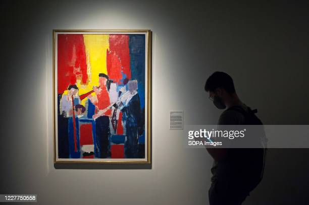Visitor wearing a face mask is seen checking his mobile phone infront a painting during the exhibition Nicolas de Staël at Museum Centre Pompidou. A...